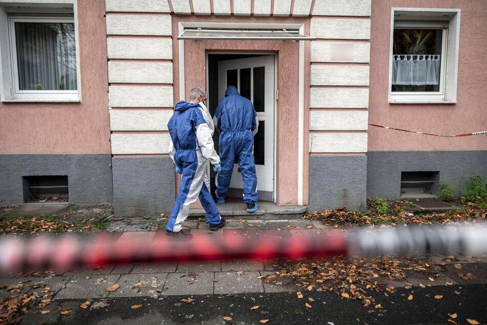 Beamte in Schutzausrüstung gehen in das Mehrfamilienhaus, das mit Polizeiband abgesperrt ist.