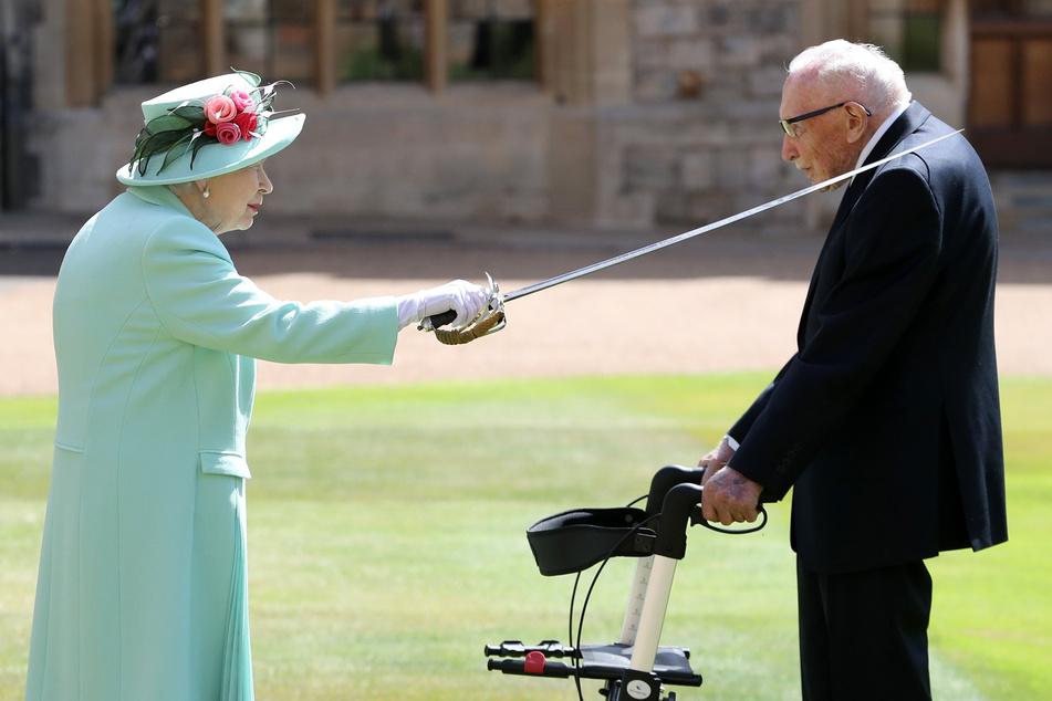 Windsor: Königin Elizabeth II. (l) schlägt Sir Tom Moore (r), Weltkriegsveteran und Rekord-Spendensammler, während einer Zeremonie im Freien auf Schloss Windsor zum Ritter.