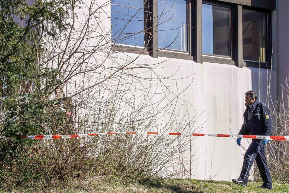 Ein Polizist läuft im März auf einem Privatgrundstück auf einer Wiese an einer Hauswand entlang. Die Polizei hatte in einem Wohnhaus die Leichen von zwei Männern und einer Frau gefunden.