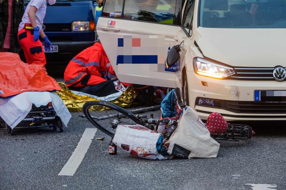 Rettungskräfte versorgen das Unfallopfer. Sein Fahrrad liegt vor dem Taxi.