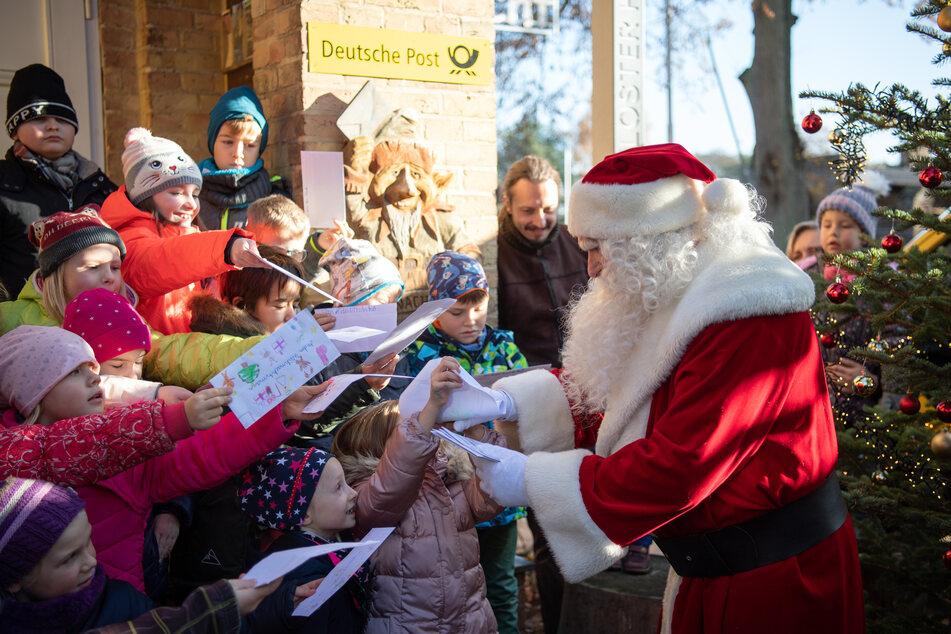 Der Weihnachtsmann wird nach seiner Ankunft vor dem Weihnachtspostamt von Kindern der Klasse 2a der Drei Seen Grundschule Fürstenberg mit Wunschzetteln begrüßt.