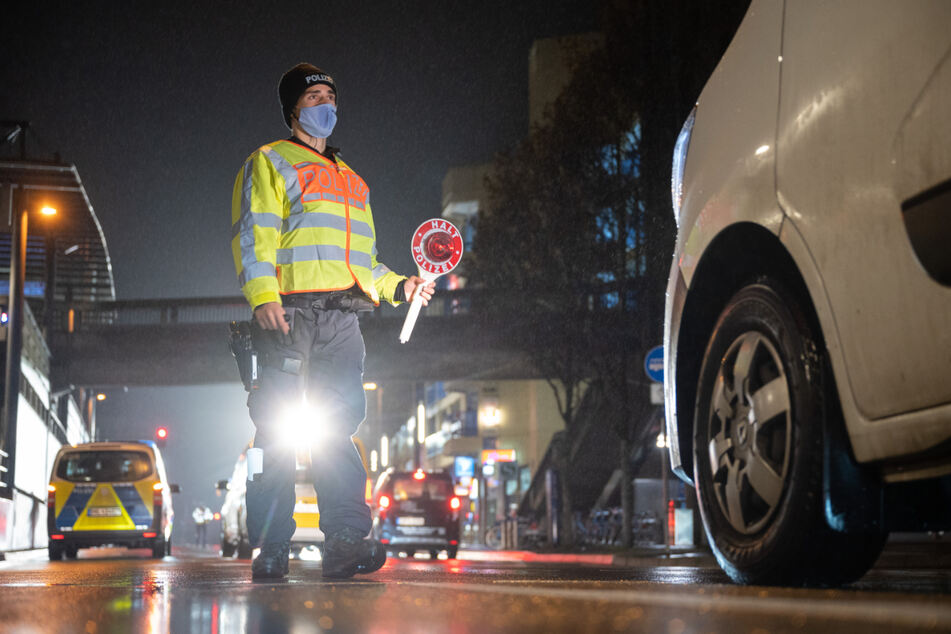 Stuttgart: Ein Polizist winkt während einer Kontrolle zur Einhaltung der Ausgangsbeschränkungen ein Auto raus.