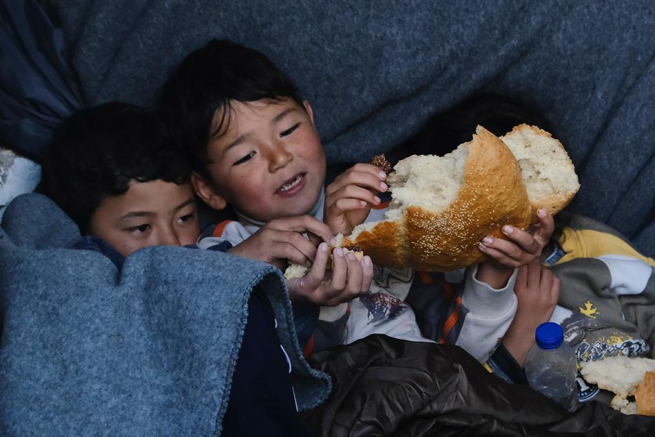 Zwei Kinder, die Anfang März aus der Türkei auf die griechische Insel Lesbos gekommen sind, liegen im Dorf Sikamineas zusammen unter einer Decke und essen Fladenbrot.