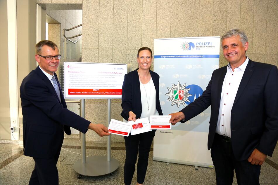 Direktor der Direktion der Kölner Kreissparkasse Wolfgang Eckert (v. l.), Kriminaloberrätin Kira Boden und Kriminaldirektor Michael Esser stellen die neuen Warnumschläge vor.