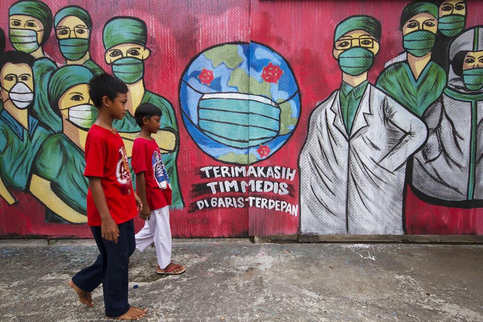 Kinder laufen vor einer Wand, an der ein Graffiti prangt, das dank gegenüber Ärzten ausdrückt.