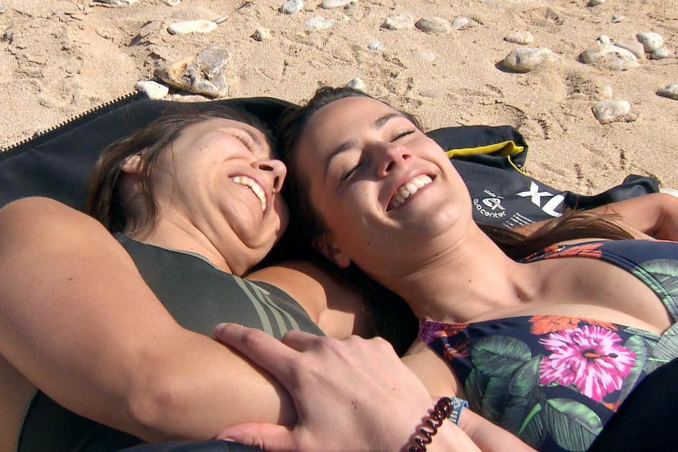 Irina (30, r.) und Miri (28) sondern sich bei Gruppendate zwischenzeitlich ab und liegen sich an einem einsamen Strand in den Armen.