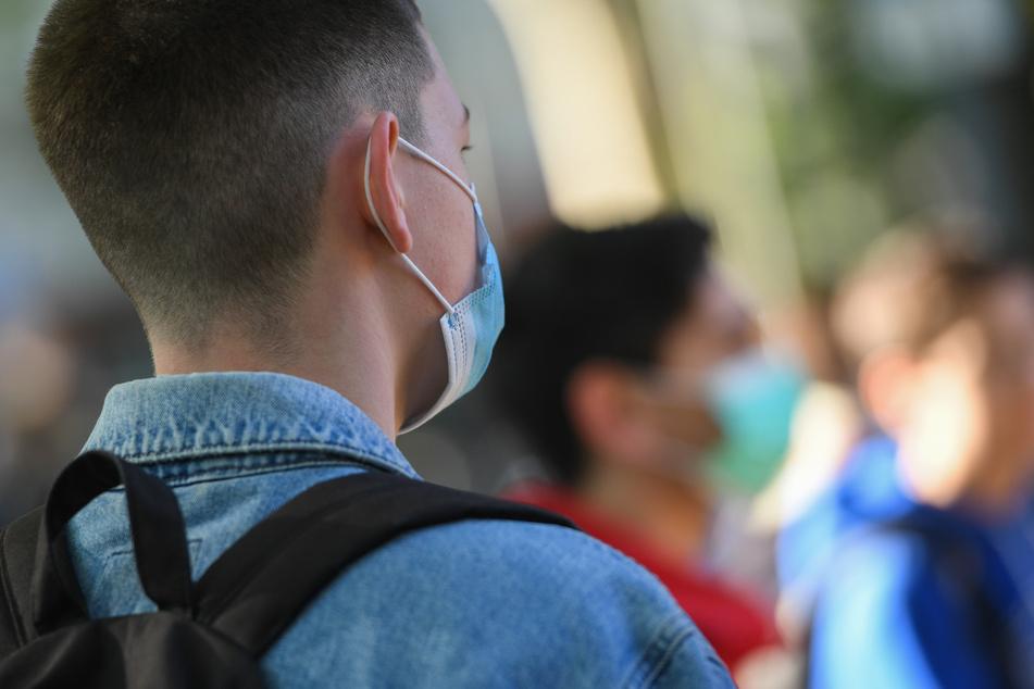 Ein Jugendlicher trägt eine Mundschutzmaske.