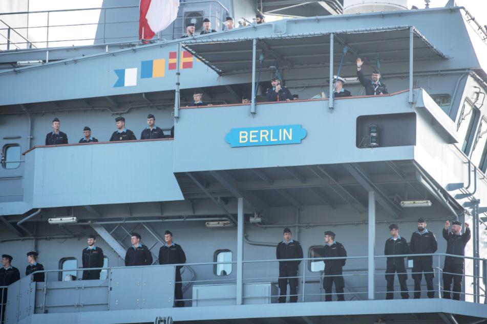 """Besatzungsmitglieder der """"Berlin"""" stehen an Deck und winken beim Einlaufen den wartenden Angehörigen zu."""