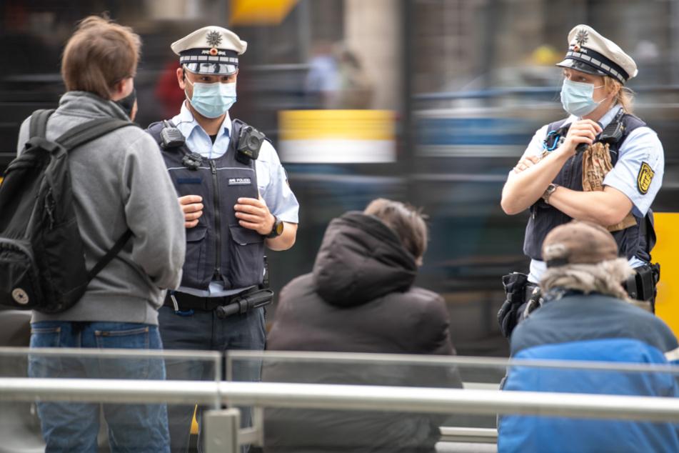 Polizeibeamte sprechen an einer Haltestelle in Stuttgart drei Männer an.