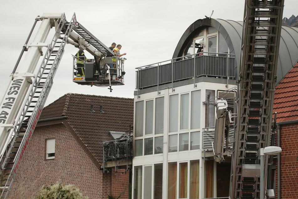 Feuerwehrleute stehen an einem beschädigten Wohnhaus auf einer Drehleiter.