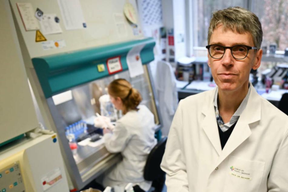 Professor Stephan Becker (r), Direktor des Instituts für Virologie der Philipps-Universität Marburg, steht in einem Forschungslabor neben einer Steril-Werkbank.