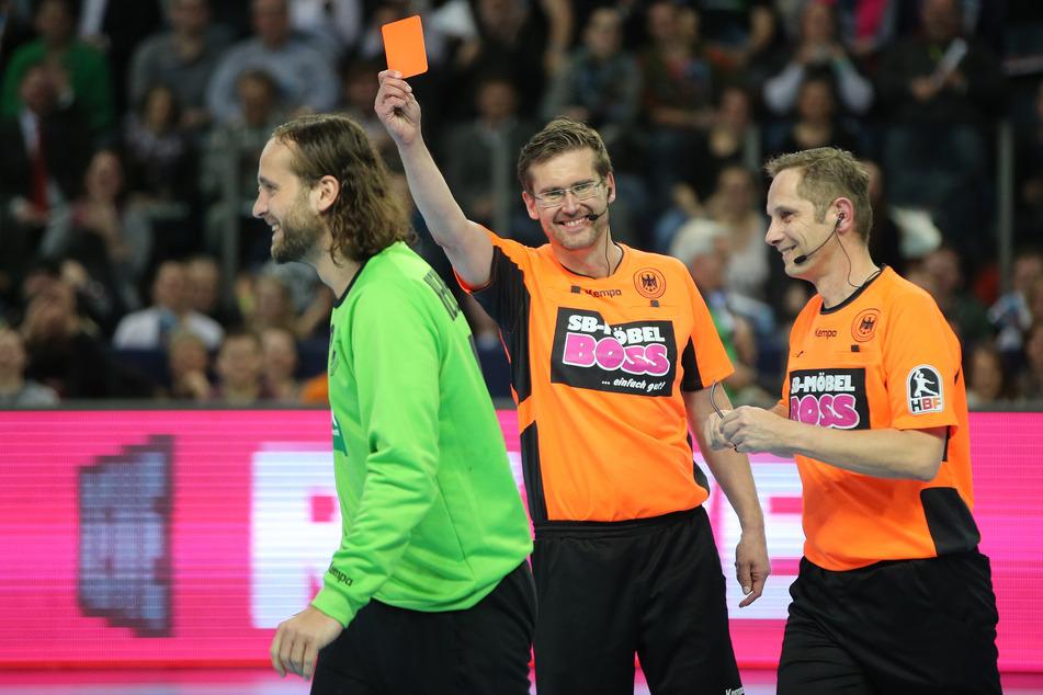 Der Schiedsrichter Lars Geipel (M) zeigt dem Nationaltorwart Silvio Heinevetter (l.) bei einem Handball Allstar Game aus Spaß die rote Karte. Rechts ist der Schiedsrichter Marcus Helbig zu erkennen.