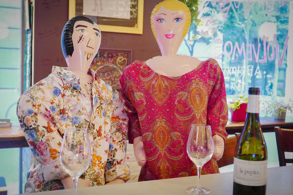 Aufblasbare Puppen sitzen an der Theke des Restaurants.