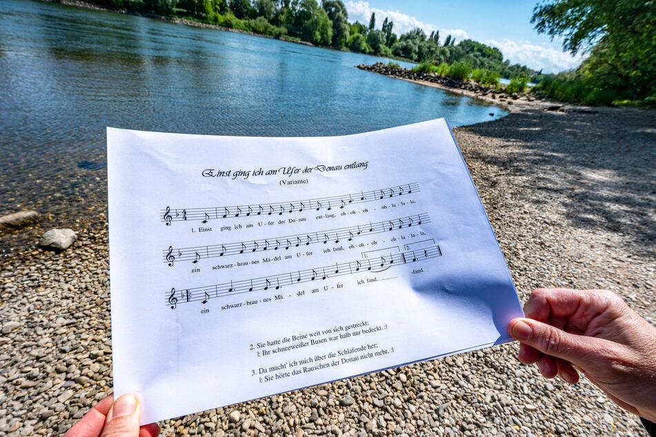 """Ein Notenblatt mit dem Liedtext """"Einst ging ich am Ufer der Donau entlang"""" wird am Donauufer gehalten."""