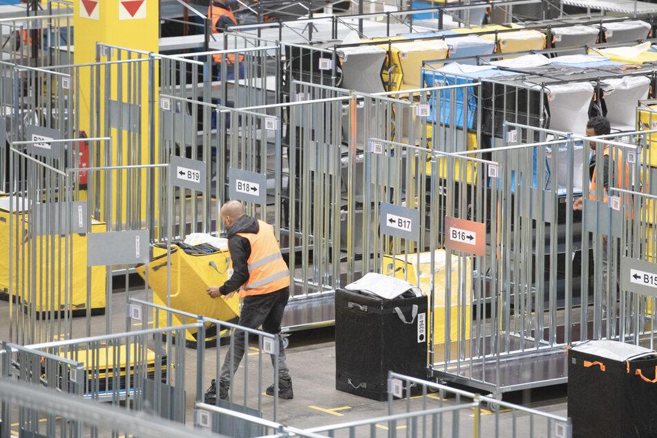 Mitarbeiter von Amazon laden in einem Verteilzentrum Pakete in verschiedene Wagen. (Symbolbild)