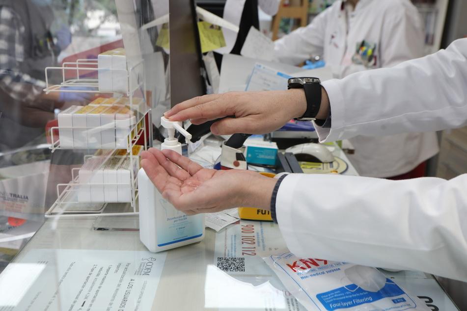 Ein Apotheker desinfiziert seine Hände. Im besonders stark von der Corona-Pandemie betroffenen Spanien ist die Zahl der bestätigten Fälle am Montag auf mehr als 200.000 geklettert.