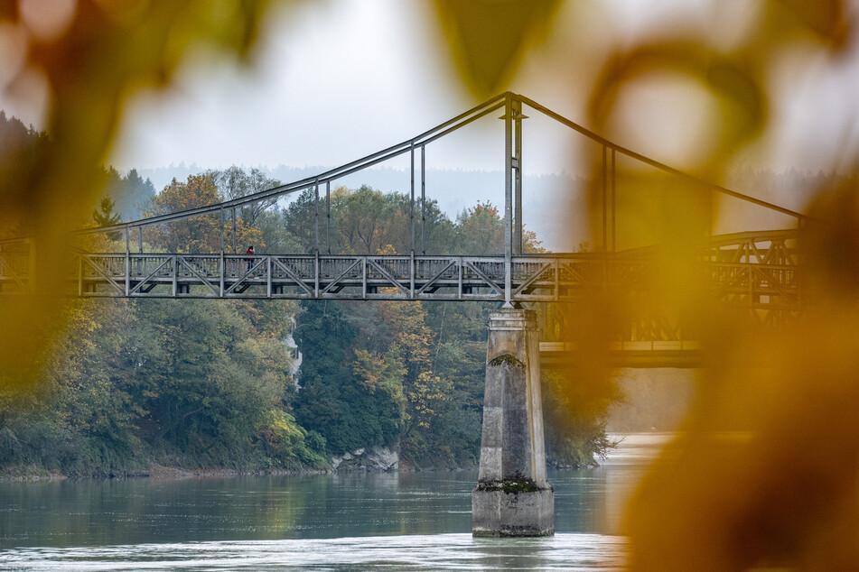 Bayern, Passau: Eine Fußgängerbrücke führt hinter herbstlich gefärbten Blättern über den Inn.