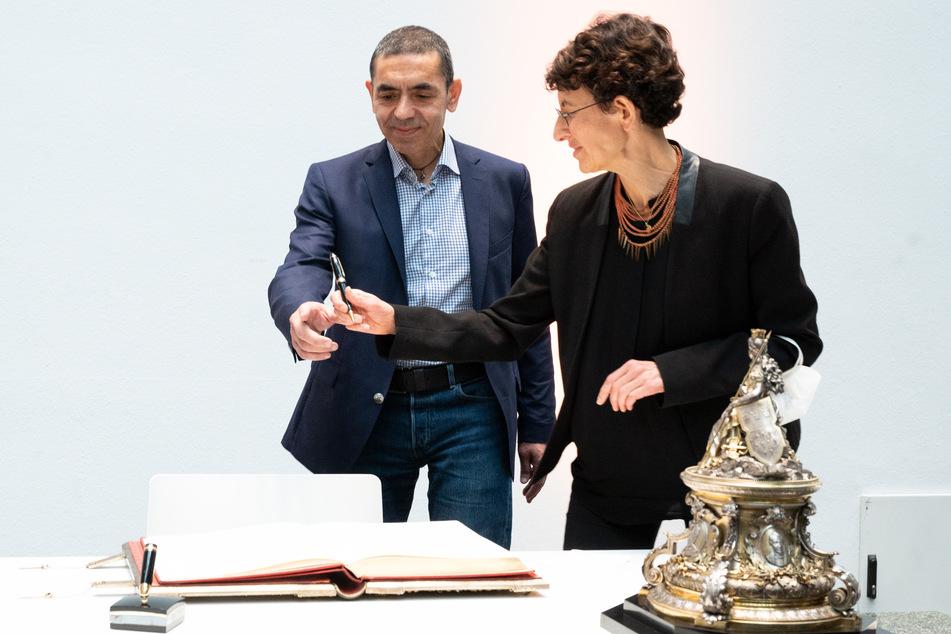 Ugur Sahin (l, 56) und Özlem Türeci (54) tragen sich in das Goldene Buch der Stadt ein und die Universität Köln verleiht die Ehrendoktorwürde.
