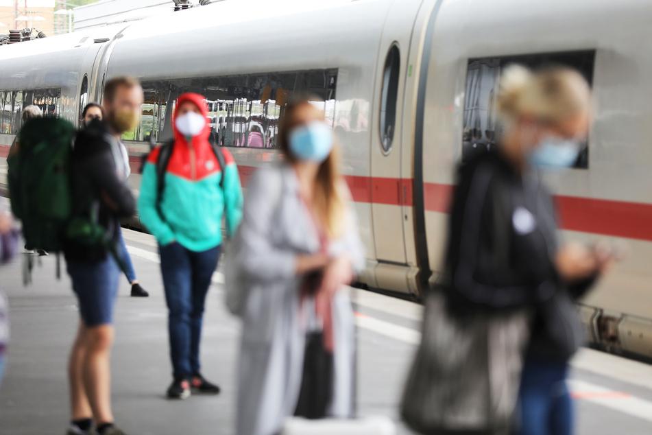 Reisende stehen auf dem Hauptbahnhof mit Masken an einem Zug. Die Bundespolizei kontrolliert zurzeit, dass auch alle Zuggäste ihre Nasen-Mund-Bedeckung anhaben.