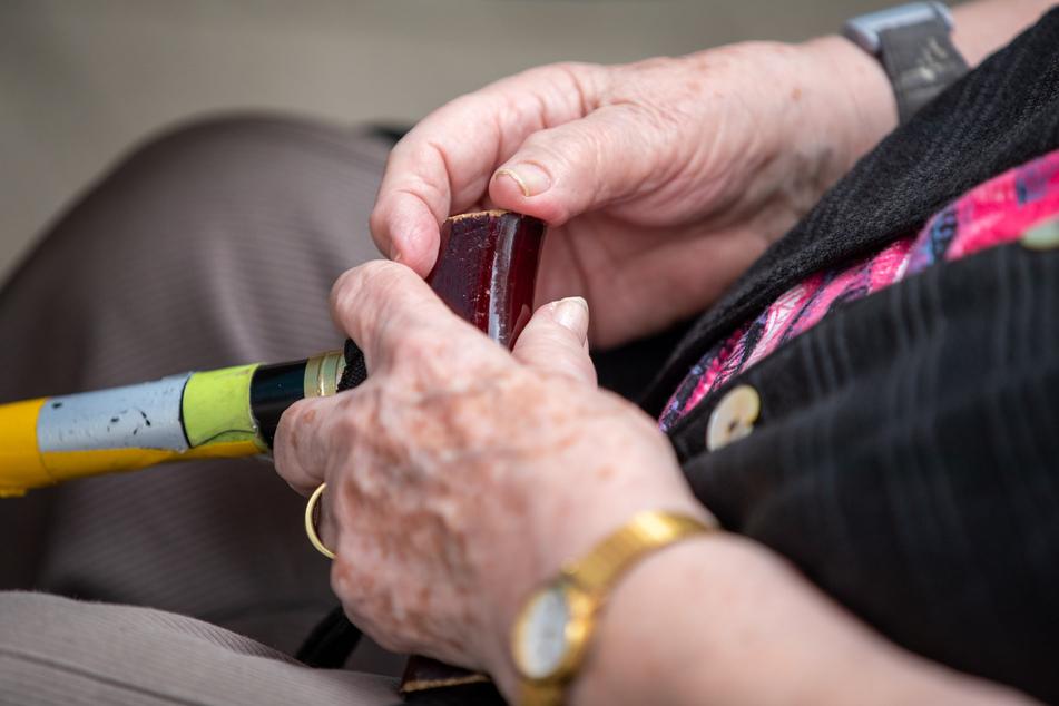 Eine Seniorin sitzt mit ihrem Gehstock im Garten eines Pflegeheimes. (Symbolbild)