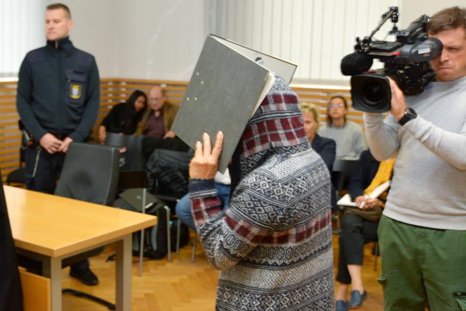 Eine mutmaßliche, angeklagte Bordellbetreiberin (m.) betritt mit verdecktem Gesicht den Gerichtssaal.