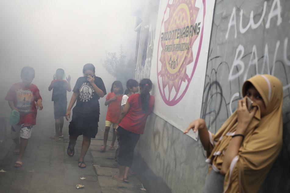 Menschen bedecken ihre Gesichter, während in großen Mengen Moskitospray im Kampf gegen das Dengue-Fieber versprüht wird. (Archivbild)