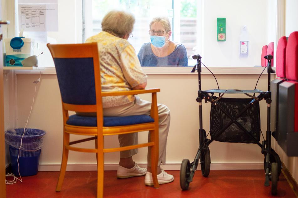Eine Besucherin unterhält sich im Besuchsraum eines Altenheimes mit ihrer Angehörigen. Dabei werden sie von einer Scheibe getrennt.