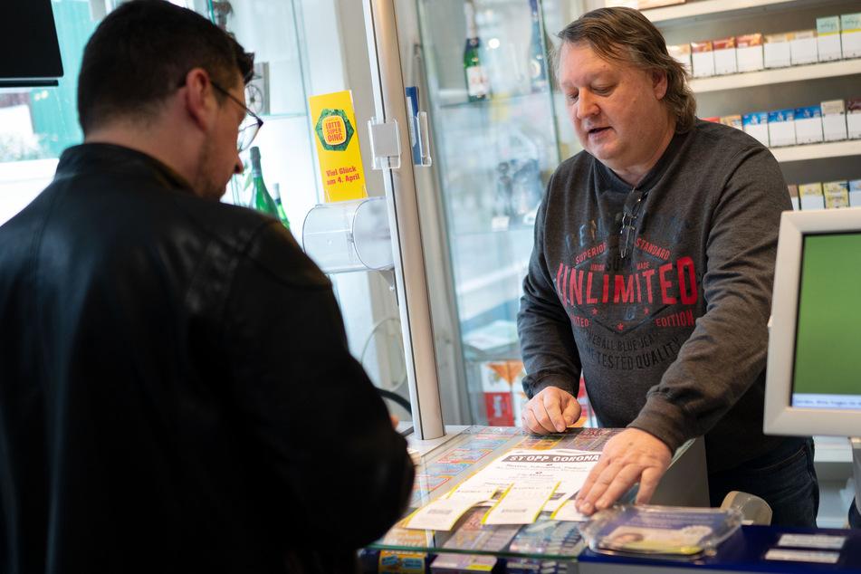 Kioskbetreiber Michael Fellendorf nimmt in seinem Geschäft einen Lottoschein an. Nicht jeder kann in Zeiten von Corona von zuhause aus sein Geld verdienen.