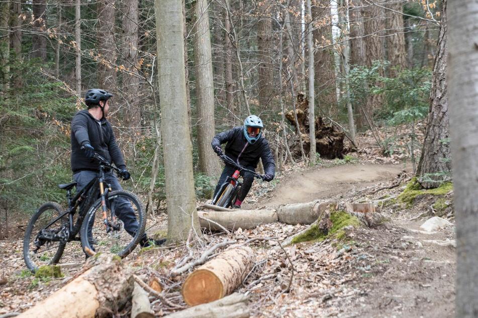 """Ein Mountainbiker fährt mit seinem Fahrrad den Trail """"Borderline"""" in Freiburg herunter, während ein anderer Mountainbiker zusieht. Der anhaltende Lockdown zieht nach Schätzungen von Experten mehr Menschen als üblich in die Wälder."""