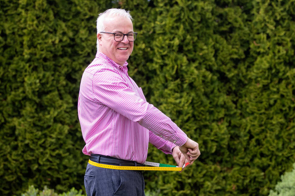 18 Kilo sind runter - Frank Schröder (52) zeigt mit dem Maßband, wie viel er abgespeckt hat.
