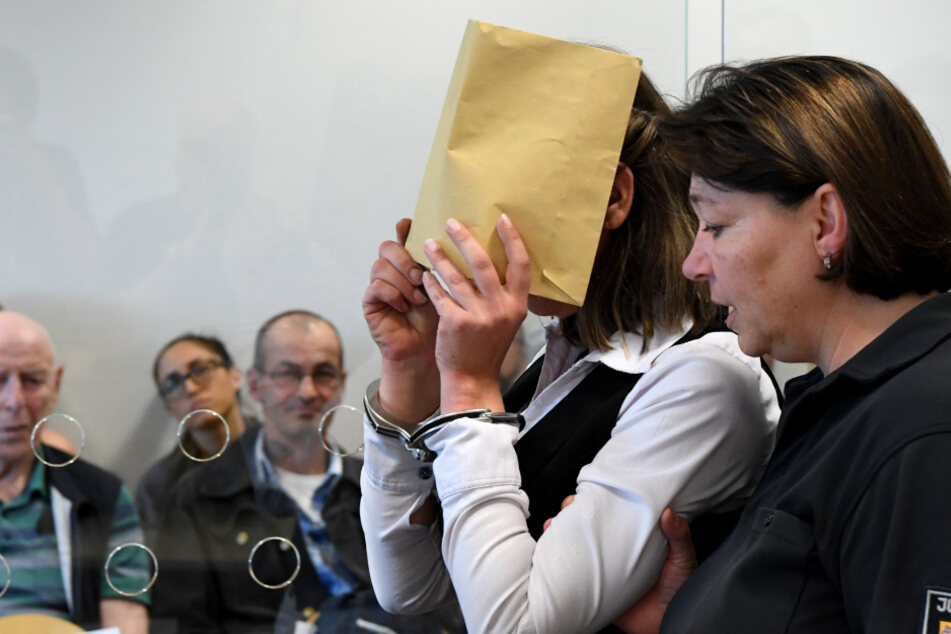 Mit verdecktem Gesicht wird die bereits verurteilte Mutter der Angeklagten in den Gerichtssaal geführt.