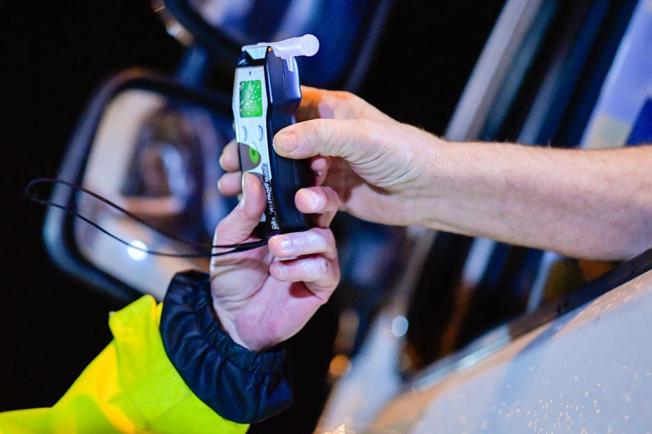 Polizisten reichen einem Fahrer ein Alkoholmessgerät. In Erfurt zogen die Beamten einen 35-Jährigen mit 3,5 Promille im Blut aus dem Verkehr. (Symbolbild)