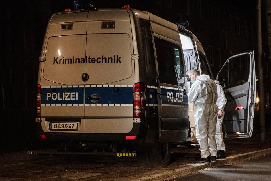 Kriminaltechniker der Polizei stehen am frühen Morgen an ihrem Einsatzfahrzeug an einem Wohnhaus im Berliner Bezirk Reinickendorf.