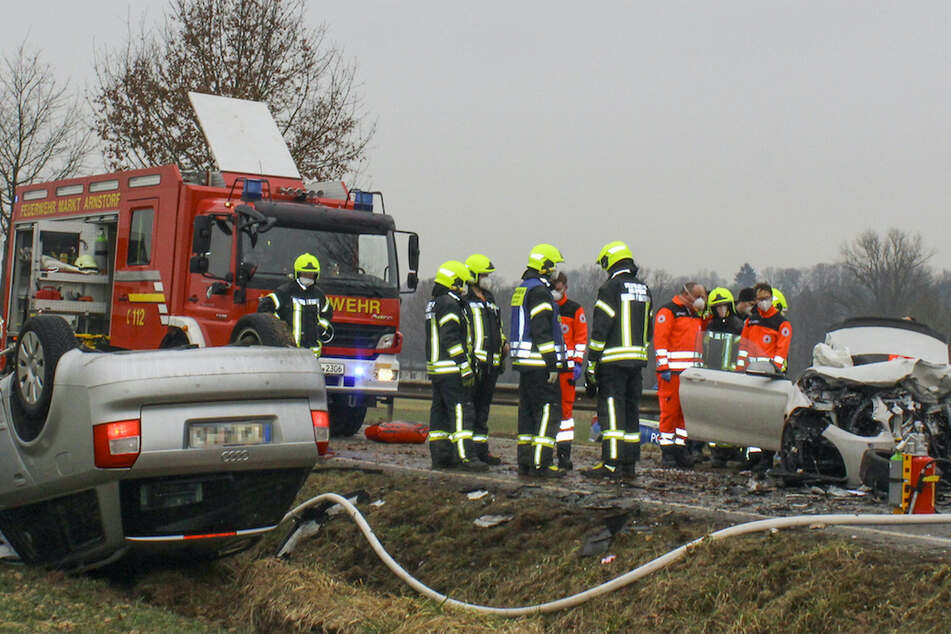 Rettungskräfte stehen am Unfallort an den Wracks der zwei Autos.