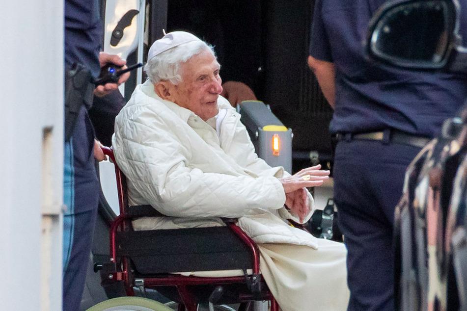 Der emeritierte Papst Benedikt XVI (93) wird mit einem Rollstuhl in einen Bus geschoben.