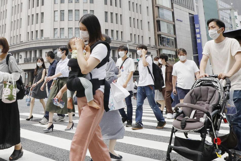 Japan, Tokio: Passanten gehen im Einkausfviertel Ginza über einen Zebrastreifen.