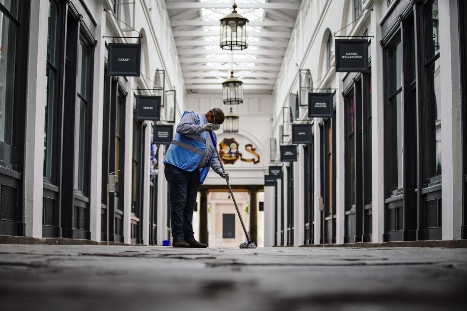 Ein Arbeiter putzt im Covent Garden in London. Großbritannien steht Experten zufolge in diesem Jahr ein erheblicher Anstieg der Arbeitslosigkeit infolge der Corona-Krise bevor.