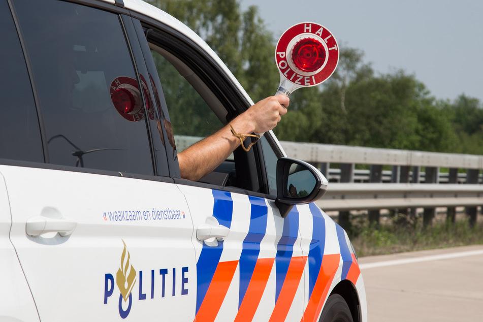 """Eine Kelle """"Halt Polizei"""" wird in Bad Bentheim aus einem niederländischen Dienstwagen des grenzüberschreitenden deutsch-niederländischen Polizeiteams."""