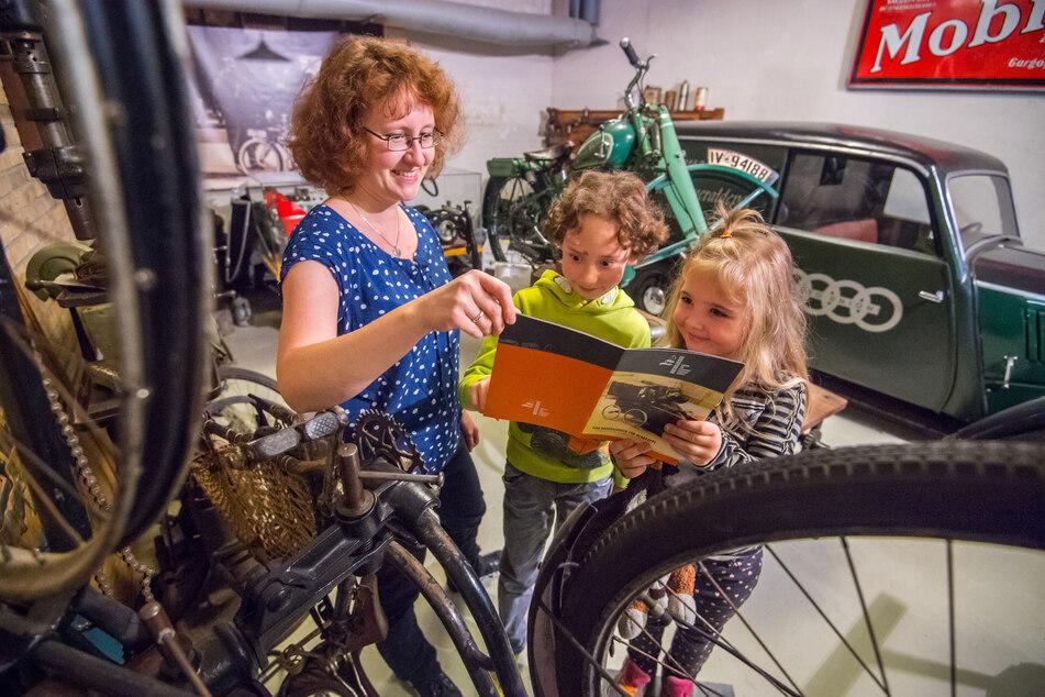 Museumsmitarbeiterin Kathy Eichholz (40) lässt Thure Eichholz (9) und Käthe Krüger (5) in die neue Broschüre für Kinder blicken.