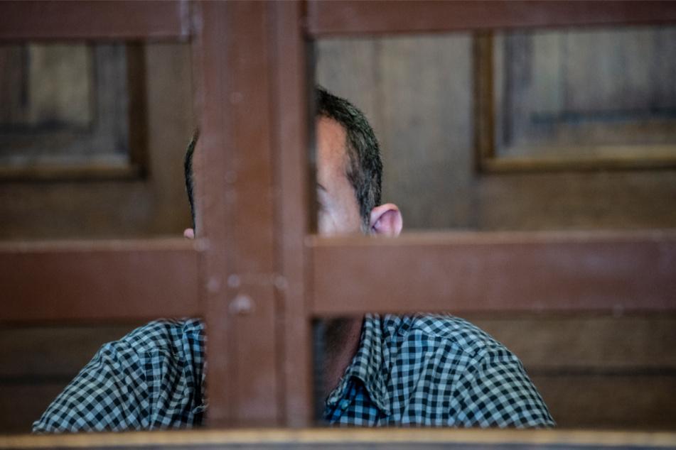Der Angeklagte sitzt vor Beginn der Verhandlung in einem Gerichtssaal.