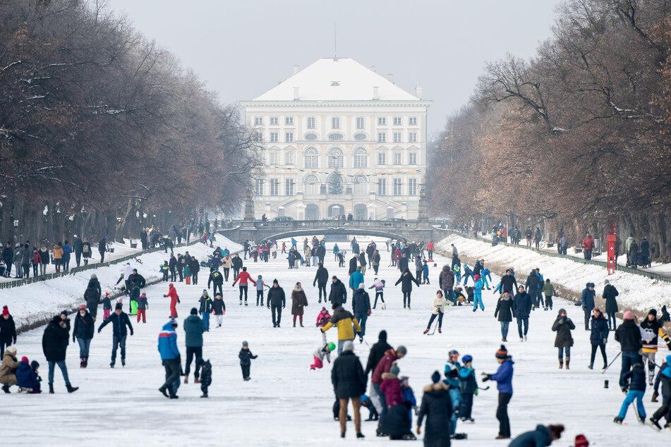 Ausflügler tummeln sich auf dem zugefrorenen Nymphenburger Kanal vor dem Nymphenburger Schloss. Ab Montag gelten wegen der Corona-Pandemie strengere Regeln.