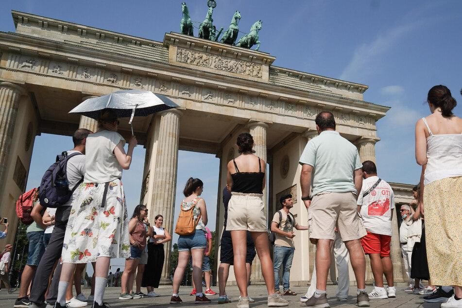Mit einem silbernen Regenschirm schützt sich die Teilnehmerin einer Stadtführung vor dem Brandenburger Tor vor den Strahlen der Sonne.