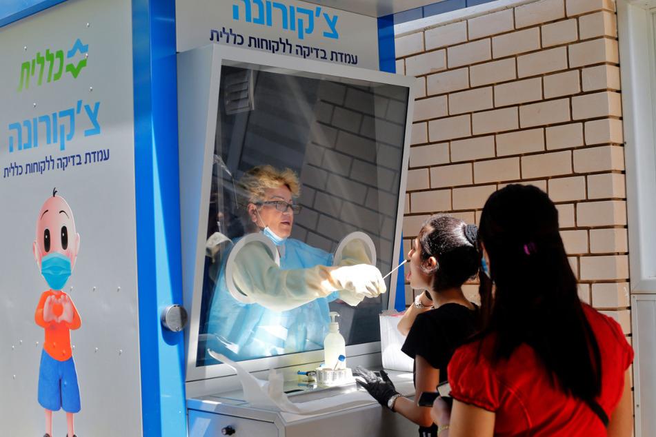 Eine medizinische Mitarbeiterin nimmt an einem Teststand in der zentralisraelischen Stadt Cholon von einer Frau einen Abstrich. Nach Angaben des Gesundheitsministeriums ist der Erreger Sars-CoV-2 bisher bei 19.783 Menschen in Israel nachgewiesen worden, 303 sind gestorben.
