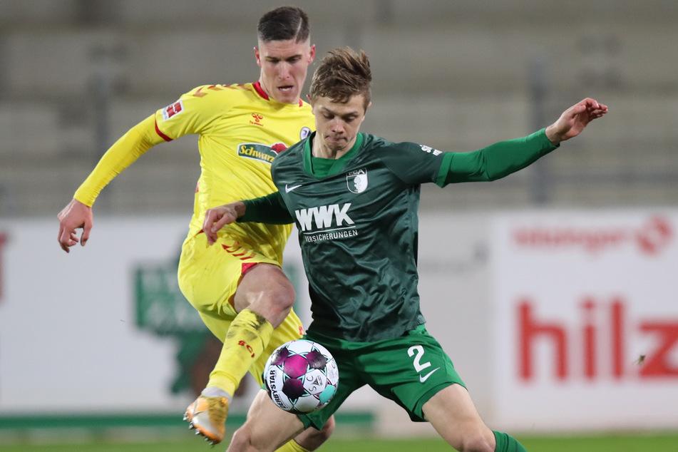Freiburg gegen Augsburg, Gelb gegen Grün, SCF-Torschütze Roland Sallai (23, l.) gegen FCA-Kicker Robert Gumny (22, r.).
