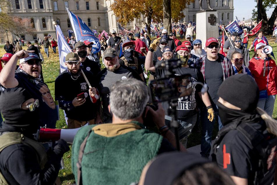 Lansing: Anhänger von US-Präsident Trump (hinten), die gegen das Wahlergebnis demonstrieren, und Gegendemonstranten geraten vor dem State Capitol aneinander.