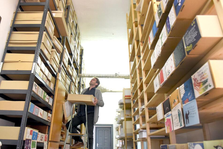 Im Archiv vom Buchkinder-Verein e.V. holt der geschäftsführende Vorstand des Vereins, Sven Riemer eine der vielen Kisten mit Manuskripten aus einem Regal. Der Verein, zu dem auch ein eigener Verlag gehört, begeht in diesem Jahr sein 20-jähriges Bestehen.