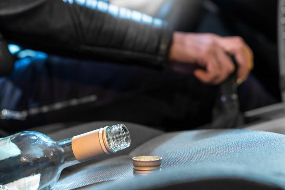 Ein Mann sitzt am Steuer eines Fahrzeugs. Auf dem Nebensitzt liegt eine leere Alkoholflasche. (Symbolbild)