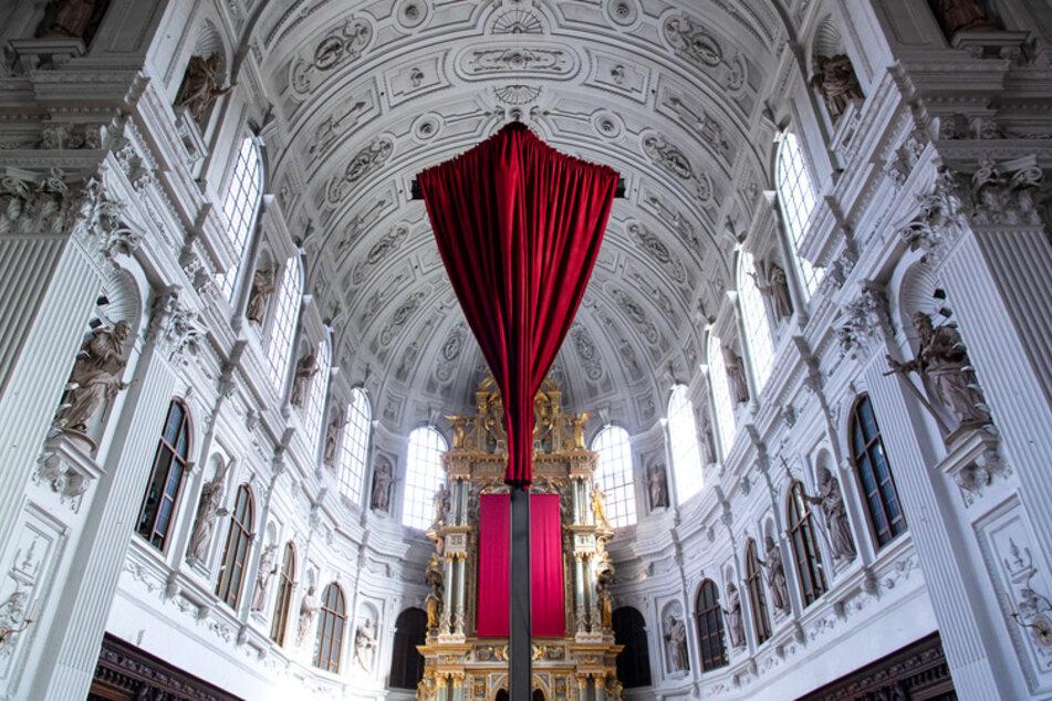Ein rotes Tuch verhüllt in der Münchner St. Michael Kirche das Kreuz vor dem Altar.