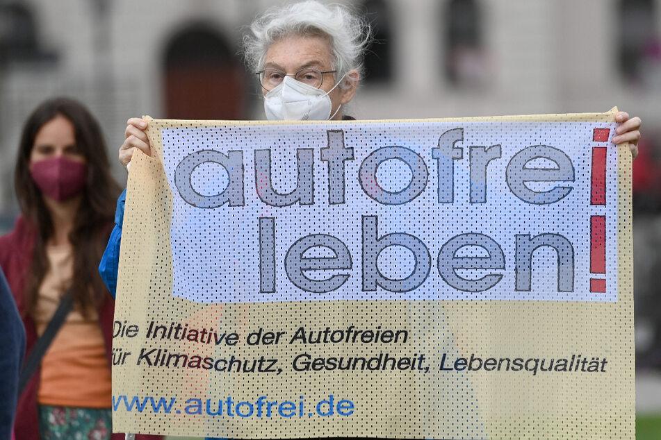 """Eine Demonstrantin hält während der Protestaktion """"Autobahn frei für IAA-Demo"""" vor dem Bayerischen Innenministerium ein Transparent mit der Aufschrift """"autofrei leben!""""."""