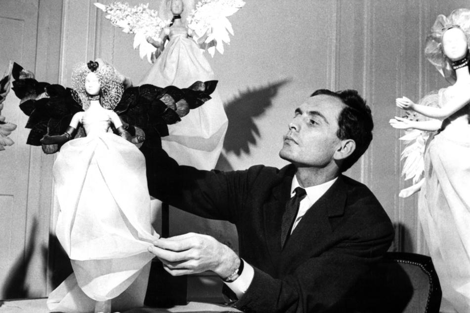 """2. Dezember 1958: Der Modeschöpfer Pierre Cardin präsentiert in Paris festlich gekleideten Puppen, die in der Vorweihnachtszeit an den Wänden seines Salons aufgestellt wurden und die seine neuesten Kreationen im """"Kleinformat"""" trugen."""